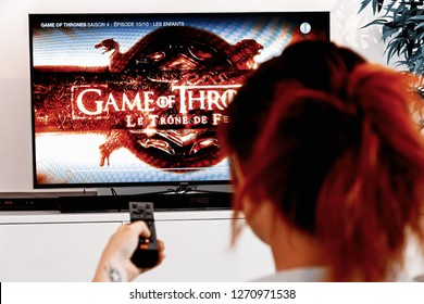 Benon, France - December 30, 2018: Woman Holding a TV remote and watch Game of thrones, an original creation of HBO industry. Created by David Benioff and D. B. Weiss, broadcast since 2011 on HBO
