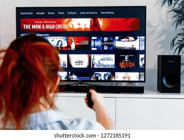 Benon, France - December 30, 2018: Woman holding a tv remote control facing a screen displaying in French language the homepage of Prime Video, a video-on-demand service created by Amazon.com
