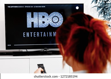 Benon, France - December 30, 2018: Woman watching tv serie produced by HBO which we see logo at the show begening. HBO is an American multinational entertainment company part of the WarnerMedia group