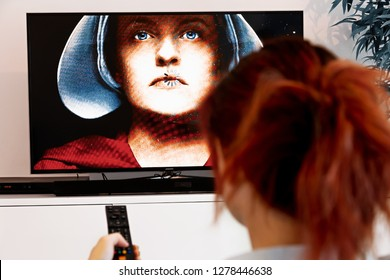 Benon, France - December 30, 2018: Woman Holding a TV remote and watch The Handmaid's Tale. The Handmaid's Tale is a futuristic drama TV series created by Bruce Miller
