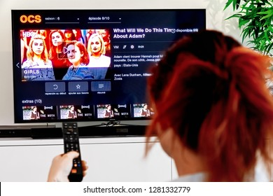 Benon, France - December 30, 2018: Woman Holding a TV remote and watch Girls, an original creation of HBO industry. Girls is an American TV series created by Lena Dunham, produced by Judd Apatow