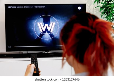Benon, France - December 30, 2018: Woman Holding a TV remote and watch Westworld, an original creation of HBO industry. Westworld is a futuristic TV series directed by Jonathan Nolan and Lisa Joy