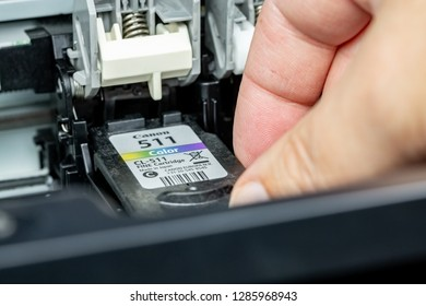 Benon, France - January 15, 2019: close up on Canon 511 Color ink cartridge replacement cartridges by one hand of a man on an inkjet printer