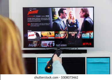 Benon, France - January 21, 2018: Woman Holding a TV remote control and play Dardevil, a Marvel film that is an original creation of Netflix industry.