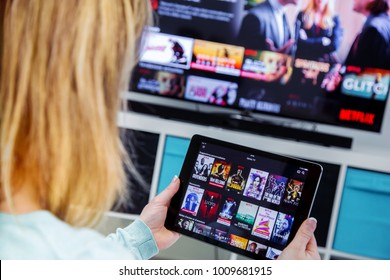 Benon, France - January 21, 2018: Woman Holding a touch pad and switching channels on France Netflix HomePage. with TV set on background.