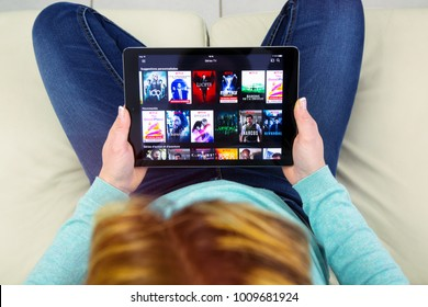 Benon, France - January 21, 2018: woman sitting cross-legged on her couch and using her touch pad to watch movies on demand on Netflix.