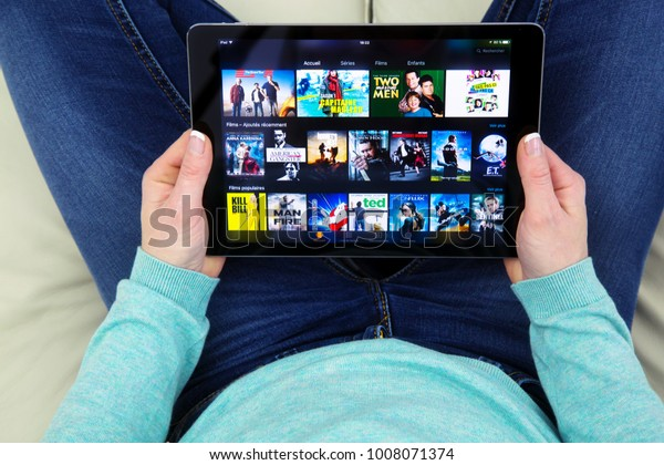 Benon, France - January 21, 2018: woman sitting cross-legged on her couch and using her touch pad to connect to watch films on the Amazon prime video app.