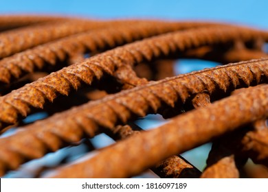 Bent and rusty iron rods or steel reinforcements on a building Site with sunlight and blue sky, selective focus and vanishing point