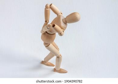 a bent wooden mannequin suffering from backache
