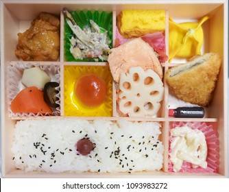Bento box. Bento is Japanese traditional takeaway lunch box divided into small section with various food and Japanese sweet i.e. salmon fish, fried chicken, potato korokke, salad & cooked vegetables