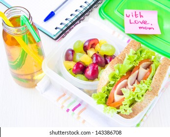 Bento lunch for your child in school, box with a healthy sandwich and fruit salad and apple juice in the bottle for drinking