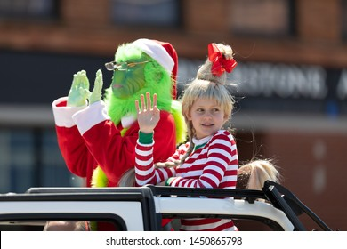 Benton Harbor, Michigan, USA - May 4, 2019: Blossomtime Festival Grand Floral Parade, Car carrying person and girl dress up as the grinch and Cindy Lou Who
