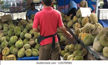 Bentong, Malaysia - July 16, 2018: Man prepares Durian for a customer at Bentong, Malaysia.