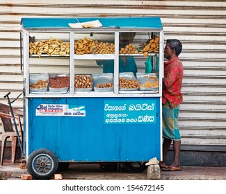 BENTOTA, SRI LANKA - APR 27: Man buys food in small portable street shops on Apr 27, 2013 in Bentota, Sri Lanka. Mobile street food sellers are popular in Sri Lanka.