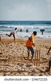 BENTOTA, SRI LANKA - APR 28:   cricket with bat and ball on sandy beach on Apr 28, 2013 in Bentota, Sri Lanka. Cricket is the most popular game in Sri Lanka.