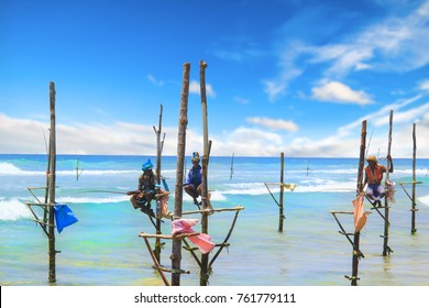 BENTOTA, SRI LANKA - MARCH 24: Several Sri Lankan fishermen men catch fish sitting on sticks on the ocean shore in Bentota on march 24 2017 on Sri Lanka