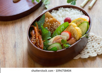 a bentwood lunch box consists of steamed rice, omelet, deep fried minced beef and the assortment of vegetables