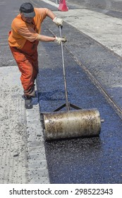 BEOGRAD, SERBIA - JULY 16, 2015: Worker using a hand roller for mastic asphalt paving. Selective focus and shallow dof, some motion blur present.