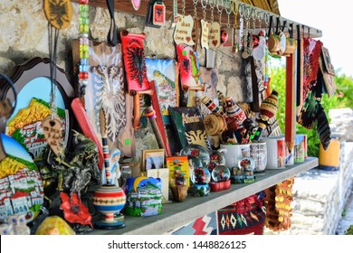 Berat, Albania - June 12 2019: Albanian souvenirs for sale at a tourist site in Berat. Items on the typical albanian street stall selling tourist souvenirs. Selective focus