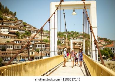 BERAT, ALBANIA - June 2018: Tourists passing modern bridge in Historical town Berat, in Albania, Unesco World Heritage Site.