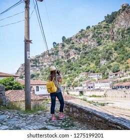 BERAT, ALBANIA - June 2018: Young woman making photo of historical town Berat, ottoman architecture in Albania, he city of a thousand windows.