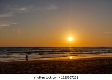 Berawa beach (Pantai Berawa) at sunset. Silhouette of a person walking along. Canggu, Bali, Indonesia.