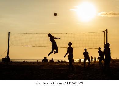 Berawa beach (Pantai Berawa) at sunset. Silhouettes of people playing volleyball. Canggu, Bali, Indonesia.