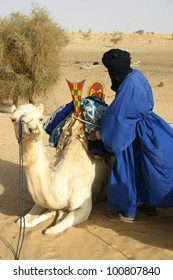 A Berber nomad from the Tuareg tribe saddles his camel in the Sahara Desert of Mali, Africa