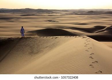 Berber Walking Along a Sand Dune
