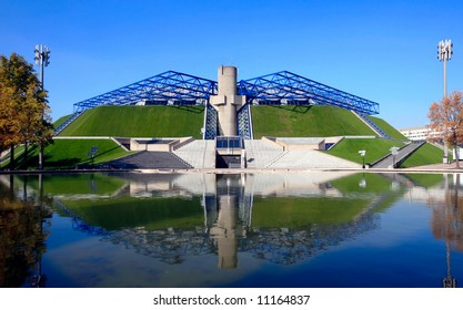 Bercy indoor arena for sports and entertainment events in Paris, France across the pond with reflection. Modern architecture inspired by ancient Egyptian pyramids.