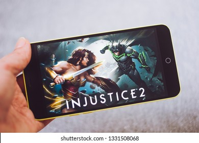 Berdyansk, Ukraine - March 4, 2019: Hands holding a smartphone with Injustice 2 game on display screen.