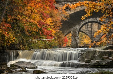 Berea Falls during peak fall colors. This cascading waterfall looks it's best with peak autumn colors in the trees. You can see the stone arch train bridges in the background crossing the Rocky River.