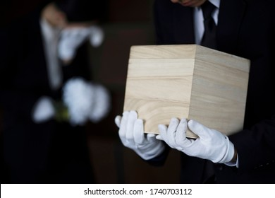 Bereaved holding urn at funeral