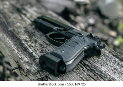 Beretta M9 Gun on the ground, police and military weapon background, black steel pistol closeup with Bokeh effect, special forces ammo. Armour and ammunition scenery, 9mm arsenal