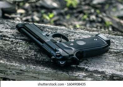 Beretta M9 police 9mm gun, black metal pistol on the ground. Special forces weapon closeup, arming scenery. Military arming and ammunition, firearms arsenal