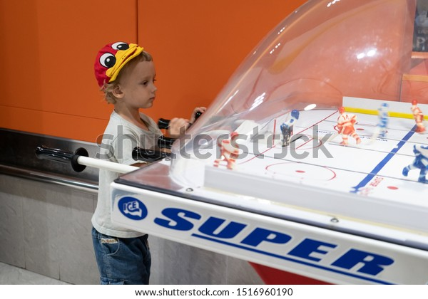 Berezovka, Russia-circa september 2019: Little boy playing in toy hockey table in room