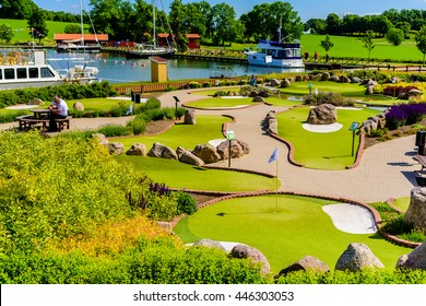 Berg, Sweden - June 20, 2016: The miniature golf course with the marina in the background. People photographing and resting on the course area.