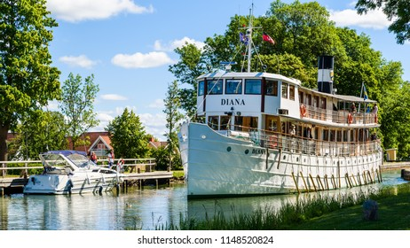 Berg, Sweden - June 30, 2018: The vintage passenger boat Diana traveling the Gota canal on an ordinary fine summer day. Here passing a motorboat moored at a boardwalk.
