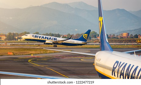 Bergamo, Italy 07/10/2018 - Boeing B737-800 Ryanair taking off from Bergamo Orio Airport at sunset with another Ryanair B737 at gate in foreground. Focus on the take off Ryanair.