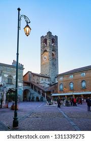 Bergamo, Italy - January 4, 2019. The Civic Tower, called Campanone, and The Palazzo del Podesta Palace in the Piazza Vecchia square at nightfall. Citta Alta, Bergamo, Lombardy, Italy.