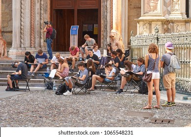 Bergamo, Italy: July 08 2017 - Architecture students drawing architectural details during en plein air assignment near Basilica of Santa Maria Maggiore in historical Upper Town.