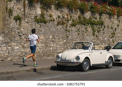 Bergamo, Italy: July 08 2017 - Vintage white Volkswagen VW Beetle cabriolet car Volkswagen Type 1, Volkswagen Bug parked on the street with a male runner approaching it.