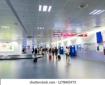 Bergamo, Italy - July 16 2018: Passengers walk at the baggage claim of Milan Bergamo airport. Unidentifiable travelers with luggage at arrivals area of Orio al Serio Caravaggio International airport.