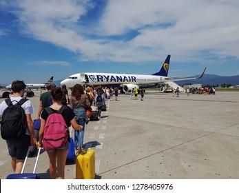 Bergamo, Italy - July 17 2018: Milan Bergamo airport tarmac passengers. Travelers with luggage at apron area of Orio al Serio Caravaggio International airport, ready to board a Ryanair aircraft.