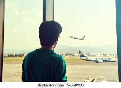 BERGAMO, ITALY - JUNE 21, 2017: Man looking at an airplane taking flight from the airport waiting area, Bergamo, Italy,