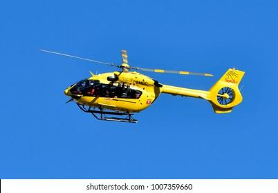 BERGAMO, ITALY-JANUARY 21, 2018: yellow hospital elichopter flying on a blue sky, in Bergamo.