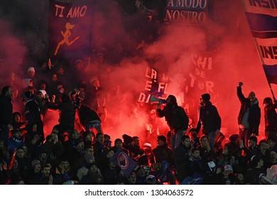 BERGAMO, ITALY-JANUARY 30, 2019: Atalanta's soccer fans cheering with red smoke bombs and waving flags, during the Italian Cup match Atalanta vs FC Juventus, in bergamo.