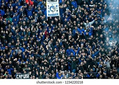 BERGAMO, ITALY-NOVEMBER 11, 2018: football fans crowd cheer on and light smoke bombs at the italian soccer stadium, Atleti Azzurri d'Italia, in Bergamo.