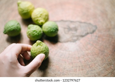 bergamot and garlic.Close up bergamot on wooden table background. with some juice,popular ingredient for Thai cuisine, also for hair shampoo or conditioner treatment. Kaffir lime