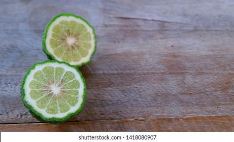 Bergamot or kaffir lime cut in half on the wooden background